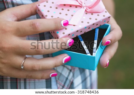 Beautiful female hands hold the box in which lie pregnancy tests - stock photo
