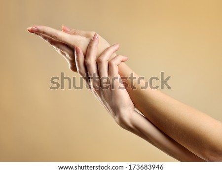 Beautiful Female Hands in golden tones. Manicure and skin care concept - stock photo