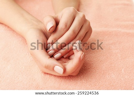 Beautiful female hands on fabric background - stock photo