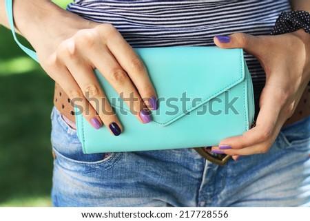 Beautiful female hands  sweet cute manicure hold blue  big purse - stock photo