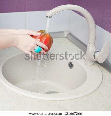 Beautiful female hands with fashionable blue ring washing red pepper (paprika) in modern kitchen. Indoor shot - stock photo