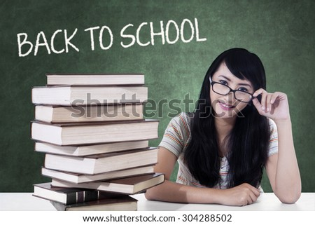 Beautiful female high school student back to school and sitting in the classroom with a pile of books on the table - stock photo
