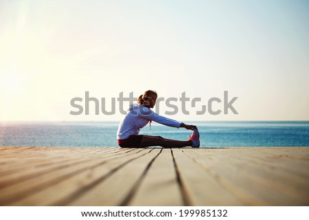 Beautiful female jogger doing workout during the morning training on the beach,workout before the morning jog along the seafront - stock photo