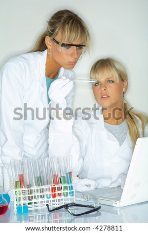 Beautiful female lab workers testing and experimenting