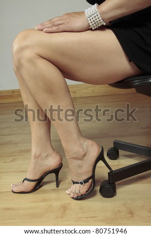 Beautiful female legs  high heels sitting - stock photo