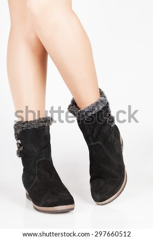 Beautiful female legs in black suede boots on a white background - stock photo