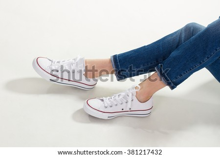 Beautiful female legs in gumshoes and jeans. Stylish youth gumshoes.