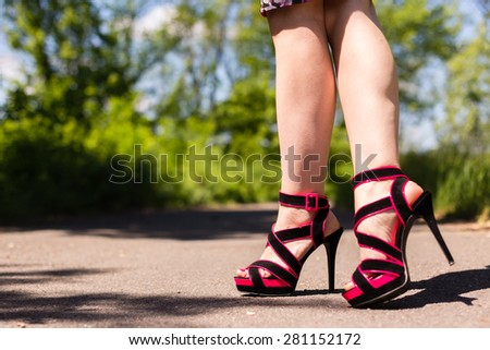 Beautiful female legs in pink shoes walking along the road - stock photo