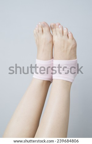 Beautiful female legs in pink socks on a gray background. Foot care - stock photo