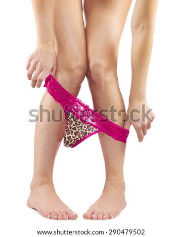 Beautiful female legs in with red lace panties off, naked. - stock photo