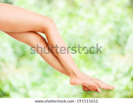 Beautiful female legs isolated on the green background