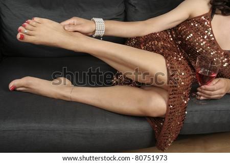 Beautiful female legs massaging aching feet wearing party dress relaxing - stock photo