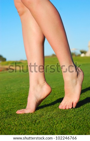 beautiful female legs on grass - stock photo