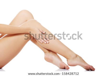 Beautiful female legs touched by hand , isolated on white  - stock photo