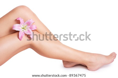 beautiful female legs with flower on white - stock photo