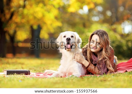 Beautiful female lying down with her labrador retriever dog in a park - stock photo