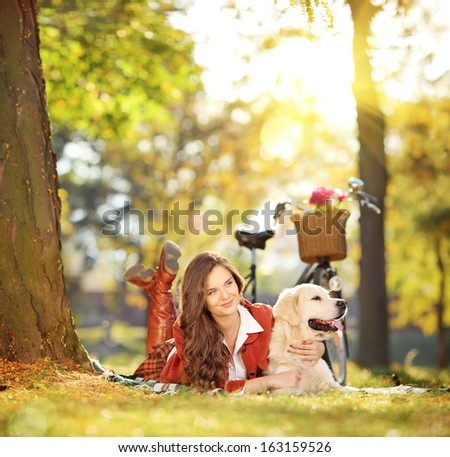 Beautiful female lying on a green grass with her labrador retriever dog in a park, shot with a tilt and shift lens - stock photo