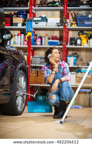 beautiful female mechanic in an auto repair shop talking on mobile