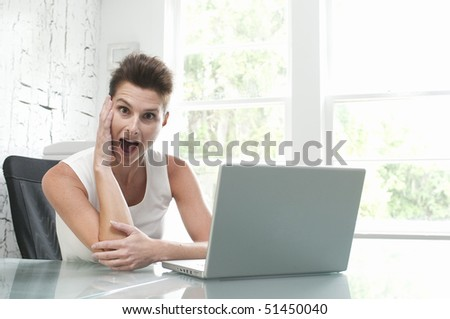 Beautiful female model at computer in bright office