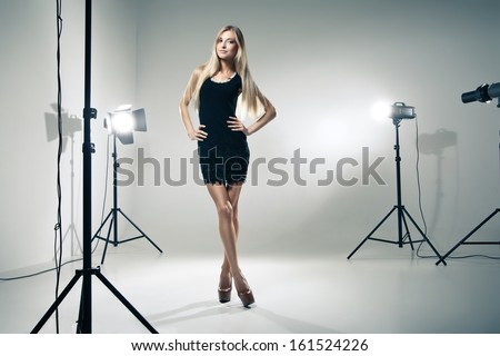Beautiful female model posing at studio in the light flashes - stock photo