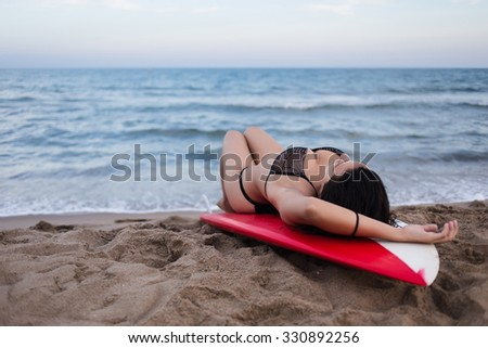 Beautiful female model posing for a women's magazine outdoors on the beach, young girl with curvy shape in sexually open bikini lying on a surfboard in seductive pose while enjoying vacation holidays - stock photo