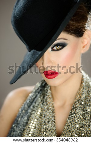 Beautiful female model with makeup wearing a hat with red lips - stock photo