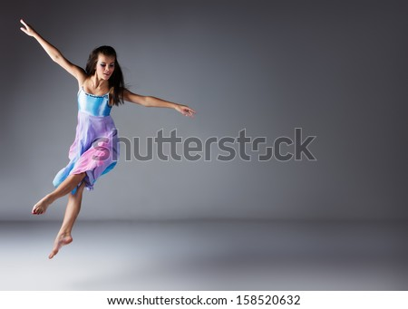 Beautiful female modern jazz contemporary style dancer on a grey background. Dancer is barefoot and wearing a blue and purple dress. - stock photo