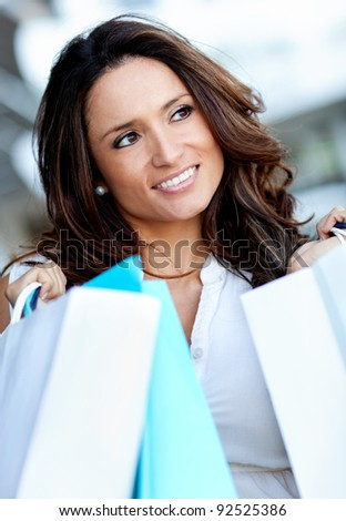 Beautiful female out shopping holding paper bags outdoors - stock photo