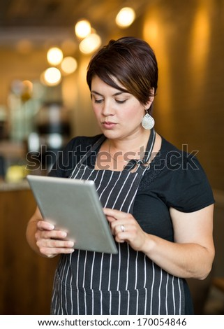 Beautiful female owner using digital tablet in coffee shop - stock photo