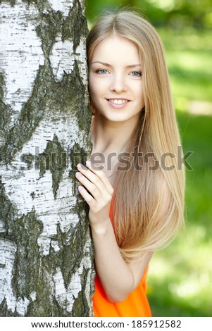 Beautiful female peeping from behind tree, against green of summer park.