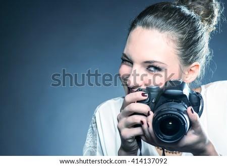 Beautiful female photographer using her camera in studio. - stock photo