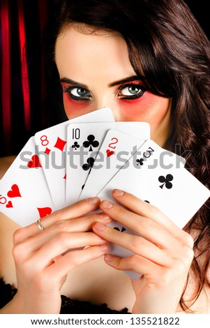 Beautiful female poker playing with elegant makeup holding a hand of playing cards inside casino - stock photo