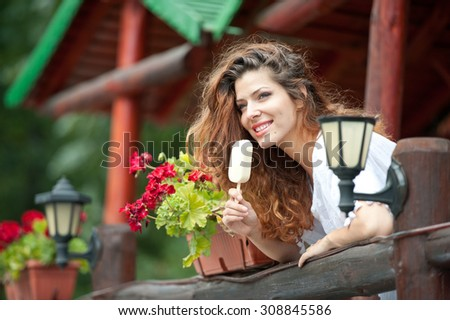 Beautiful female portrait with long brown hair eating ice cream near a pot with red flowers outdoor. Attractive woman with beautiful eyes smiling enjoying an ice cream in a summer day, outdoor shot