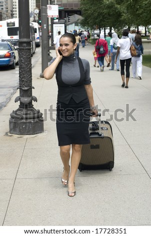 Beautiful female pulling luggage while walking downtown on a sunny day - stock photo