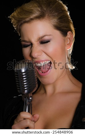 Beautiful female rocksinger screaming into Elvis microphone - stock photo