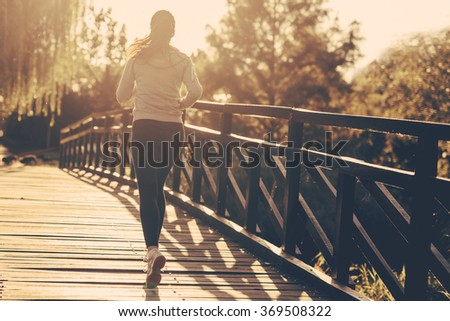 Beautiful female runner jogging in nature - stock photo
