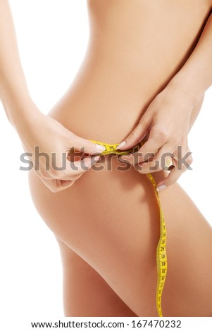 Beautiful female's thigh with measuring tape. Isolated on white. - stock photo