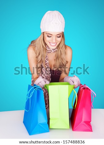 Beautiful female shopper checking her purchases peering inside the centre one of three colourful shopping bags with a wide smile of delight - stock photo