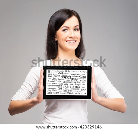 Beautiful female showing tablet on isolated background. Learning different languages concept. - stock photo