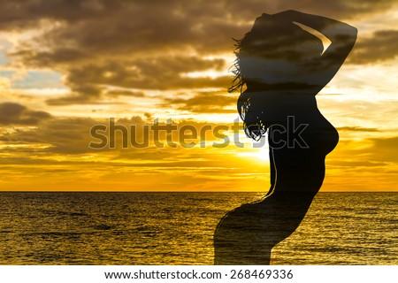 beautiful female silhouette on sunset sea background - stock photo