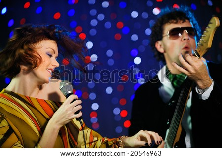 Beautiful female singer and male guitar player - stock photo