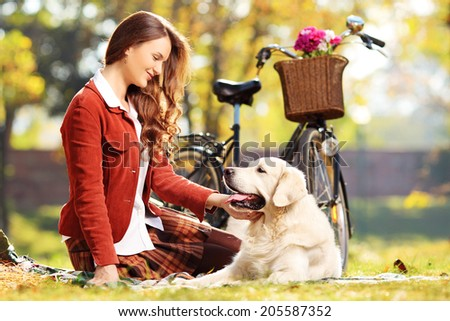 Beautiful female sitting on a grass and looking at her labrador retriever dog in a park - stock photo