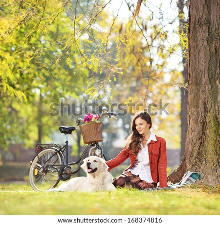 Beautiful female sitting on a green grass with her labrador retriever dog in a park, shot with a tilt and shift lens - stock photo