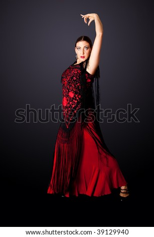 Beautiful female Spanish Flamenco dancer doing a typical line pose, wearing modern attire. Spanish woman dancing Paso Doble in red and balck dress clothes, isolated.