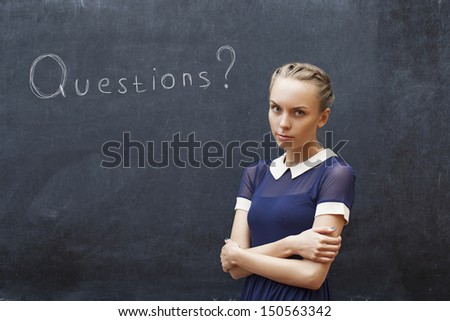 Beautiful female student at the blackboard with the words