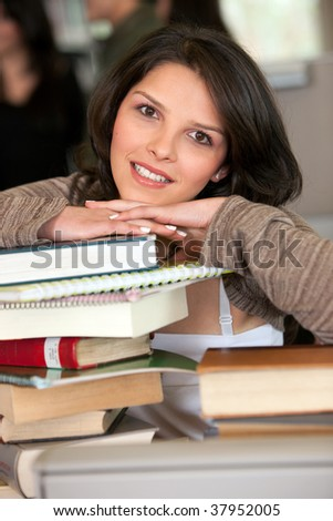 Beautiful female student at the library with books - stock photo
