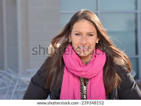 Beautiful female student (brunette) sitting outside in late fall or winter portrait - stock photo