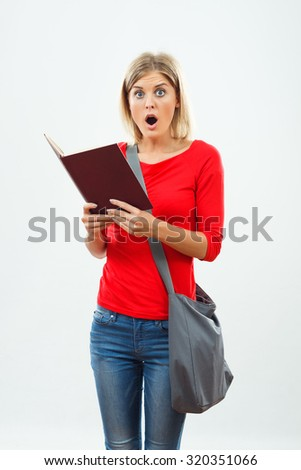 Beautiful female student is surprised because of something she had read in the book. Surprised student - stock photo