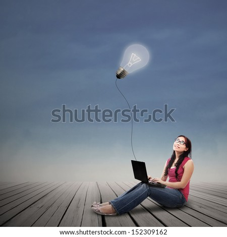Beautiful female student looking at lit bulb with laptop outdoor - stock photo