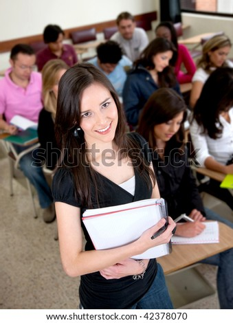 Beautiful female student smiling in a classroom - stock photo